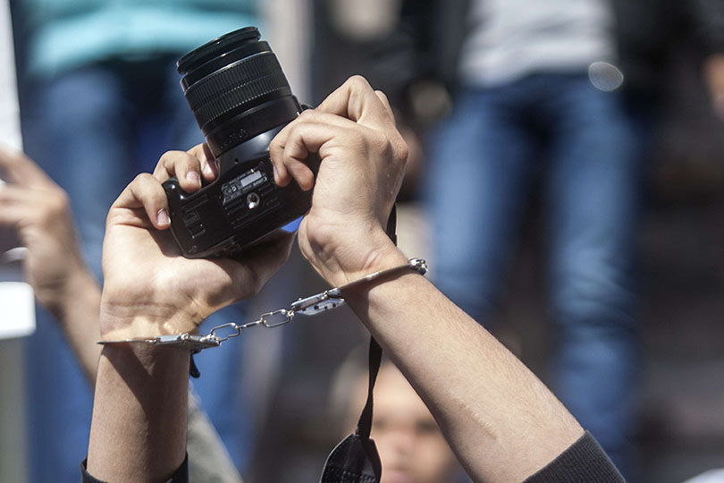 A photojournalists with his mouth tapped holds up his camera as he demonstrates with fellow colleagues in front of the journalist's syndicate in Cairo against repeated attacks on members of the press in Egypt on April 4, 2014. AFP PHOTO / MAHMOUD KHALED